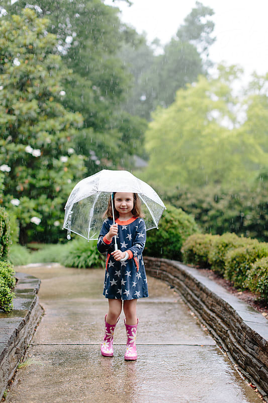 Cute young girl standing in the rain with an umbrella by Jakob for Stocksy United