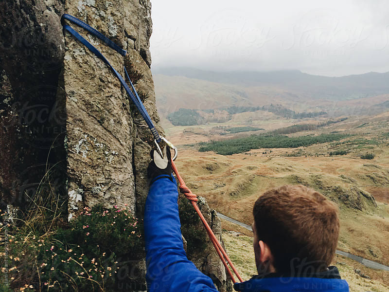 Mountaineer setting up sling for an anchor point.  by Liam Grant for Stocksy United