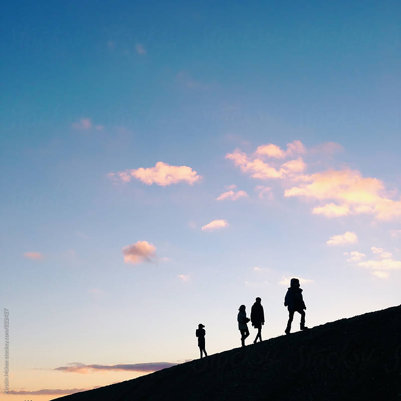 Silhouettes of people walking at sunset.  by Kirstin Mckee for Stocksy United