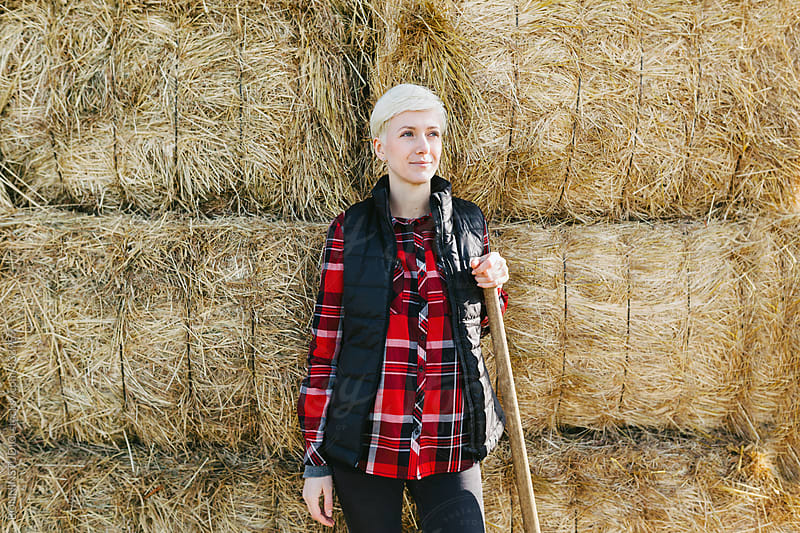 Portrait of a woman farmer with a hoe standing on a haystack. by BONNINSTUDIO for Stocksy United
