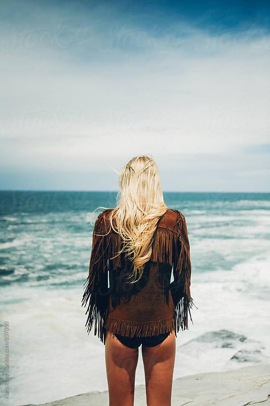 Woman facing ocean by Kara Riley for Stocksy United
