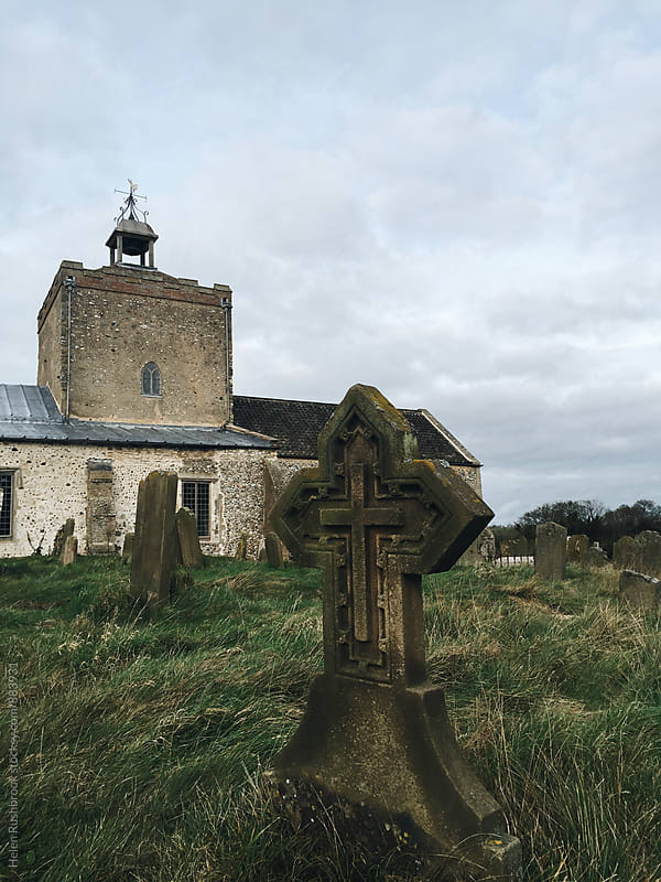 Gravestone and medieval church in Norfolk, UK. by Helen Rushbrook for Stocksy United