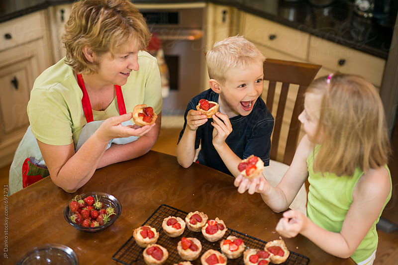 Grandmother and Grandchildren Enjoying Pastry Custard and Strawberry Tarts from Scratch Together by JP Danko for Stocksy United