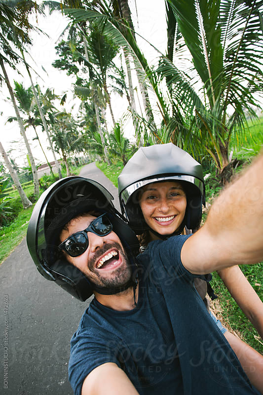 Couple taking a selfie on a motorcycle in the roads of Bali. by BONNINSTUDIO for Stocksy United
