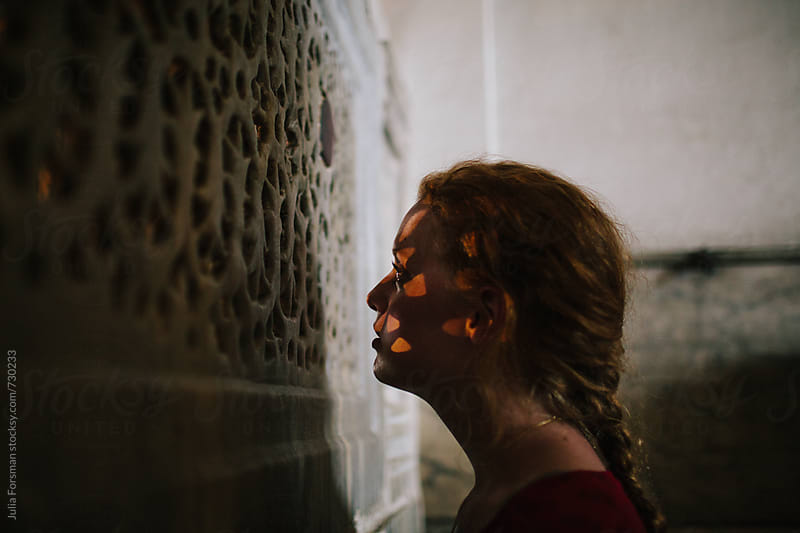 A young woman gazes through a carved stone screen in a historical building. by Julia Forsman for Stocksy United