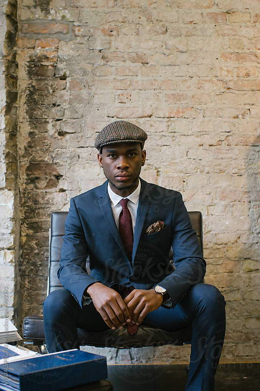 Indoor Portrait of Sitting Stylish Young Black Man in Blue Suit by VISUALSPECTRUM for Stocksy United