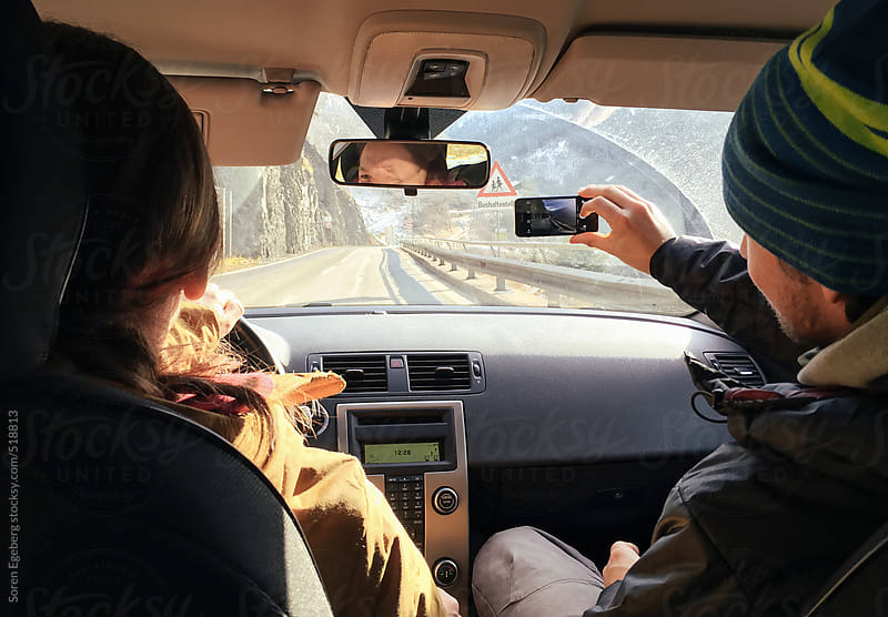 Inside view of couple driving car on mountain road trip by Soren Egeberg for Stocksy United
