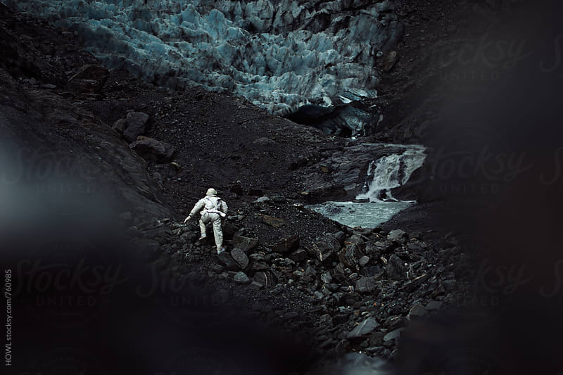 A lone astronaut climbs the side of a rocky, icy mountain.  by HOWL for Stocksy United