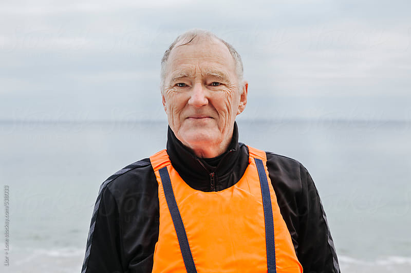 Portrait of senior man in life vest  by Lior + Lone for Stocksy United