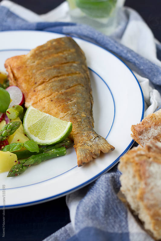 Fried fish with potato and aspragus salad by Noemi Hauser for Stocksy United