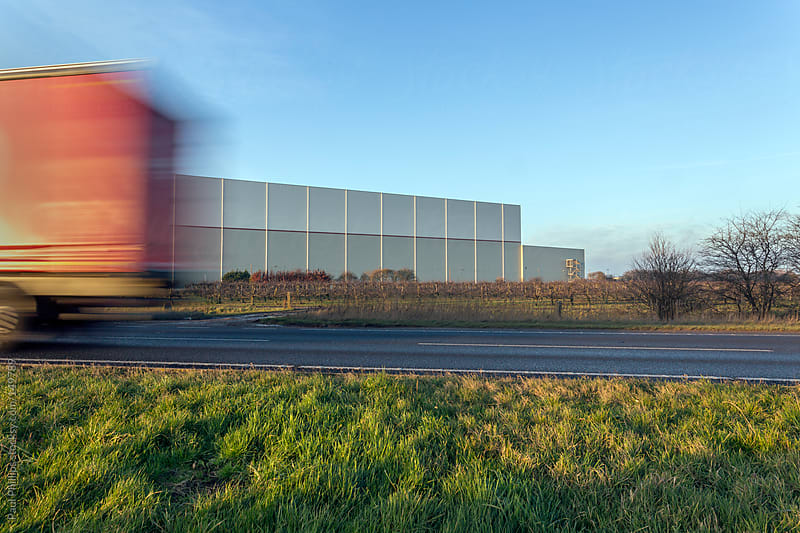 Truck moving past a warehouse (distribution centre) on an adjacent road  by Paul Phillips for Stocksy United