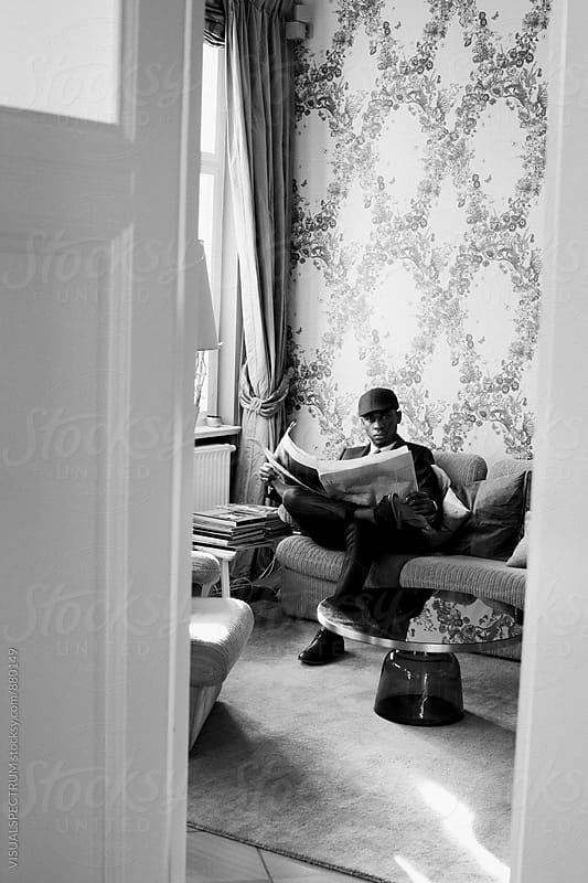 Black and White Shot of Elegant Young Black Man Reading Newspaper in Stylish Living Room by Julien L. Balmer for Stocksy United