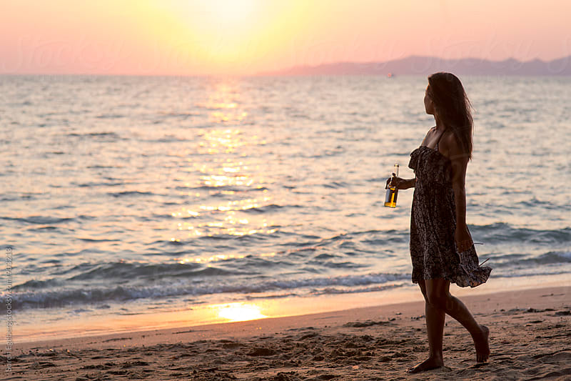 Woman walking on beach at sunset with a beer by Søren Egeberg Photography for Stocksy United