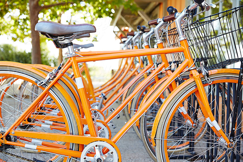 Row of orange bikes by Trinette Reed for Stocksy United