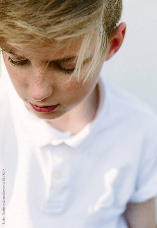 Blonde teenage boy looking down by Helen Rushbrook for Stocksy United