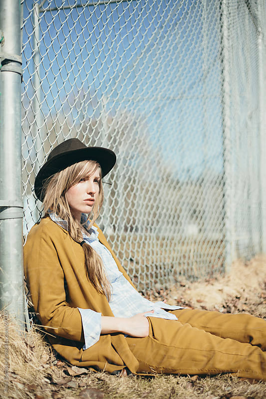 Girl sitting and leaning against a fence by Ania Boniecka for Stocksy United