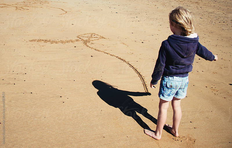 A little girl and a kite drawn into the sand on a beach by Helen Rushbrook for Stocksy United
