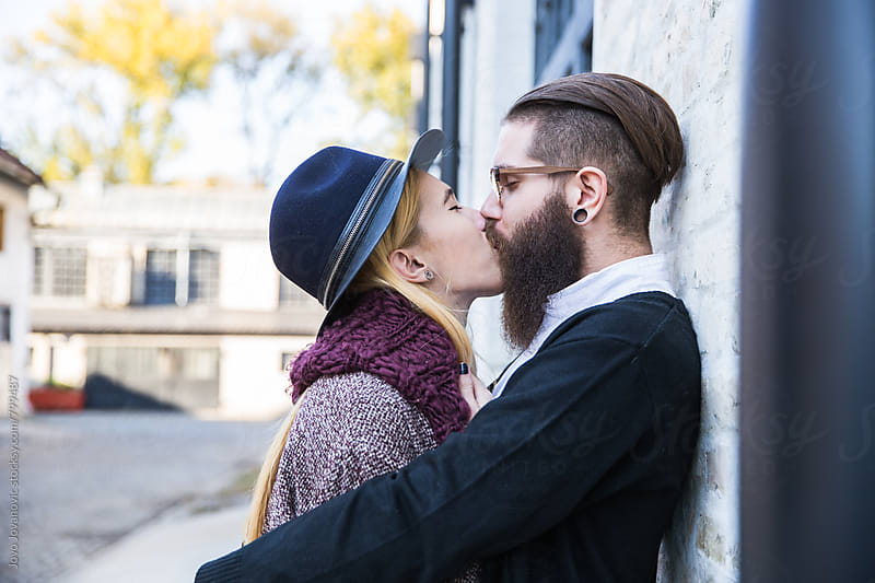 Couple kissing at alley in city by Jovo Jovanovic for Stocksy United