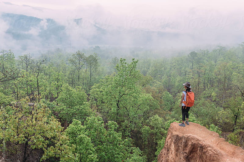 Hiker wearing backpack looking a misty mountain view by Soren Egeberg for Stocksy United