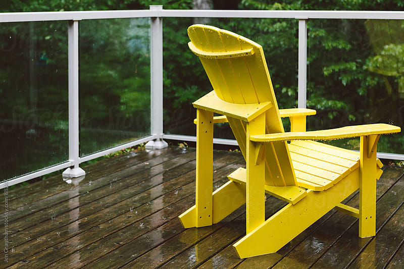 Adirondack chair outdoors in the rain by Jen Grantham for Stocksy United