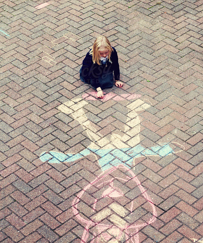 A little girl drawing with chalk on a pavement. by Helen Rushbrook for Stocksy United