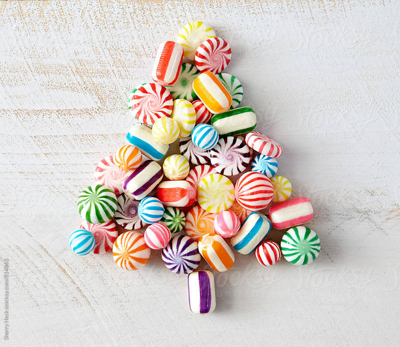 Colorful, hard, candy pieces arranged in tree shape on white surface by Sherry Heck for Stocksy United