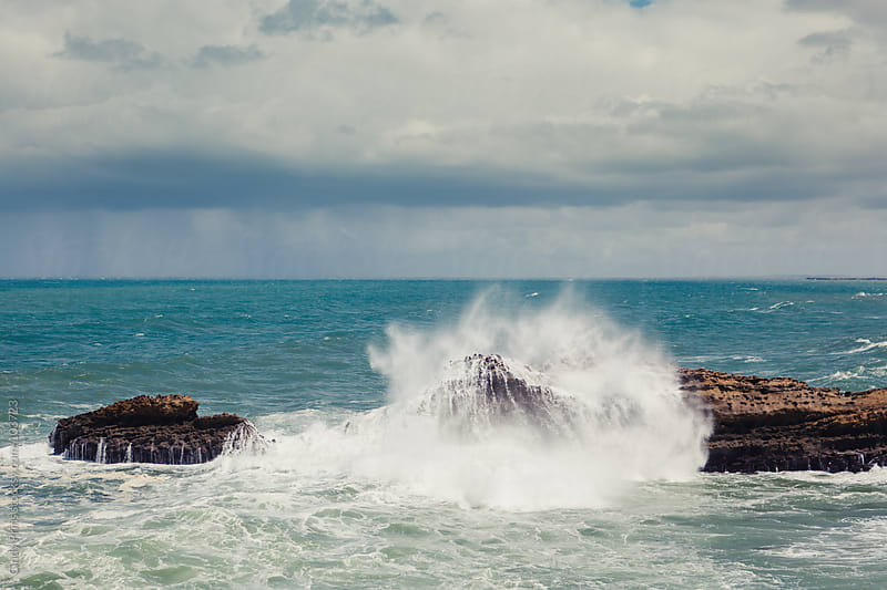 Water splashing against a rock in the ocean on a stormy summer day by Cindy Prins for Stocksy United