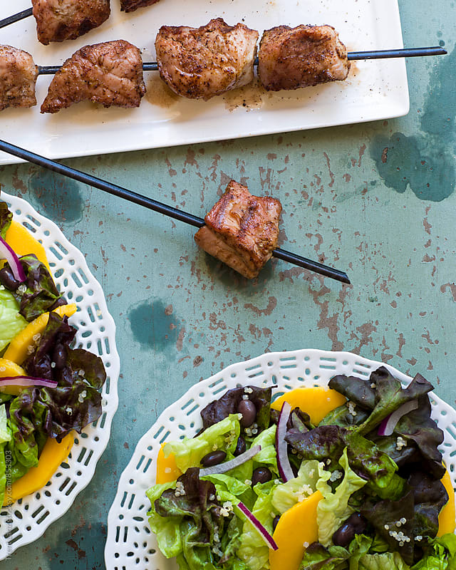 Healthy salad with mango and kebab by Trent Lanz for Stocksy United