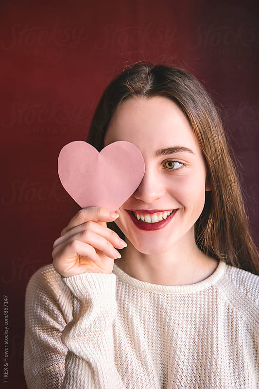 Portrait of young woman holding cut pink heart  by Danil Nevsky for Stocksy United