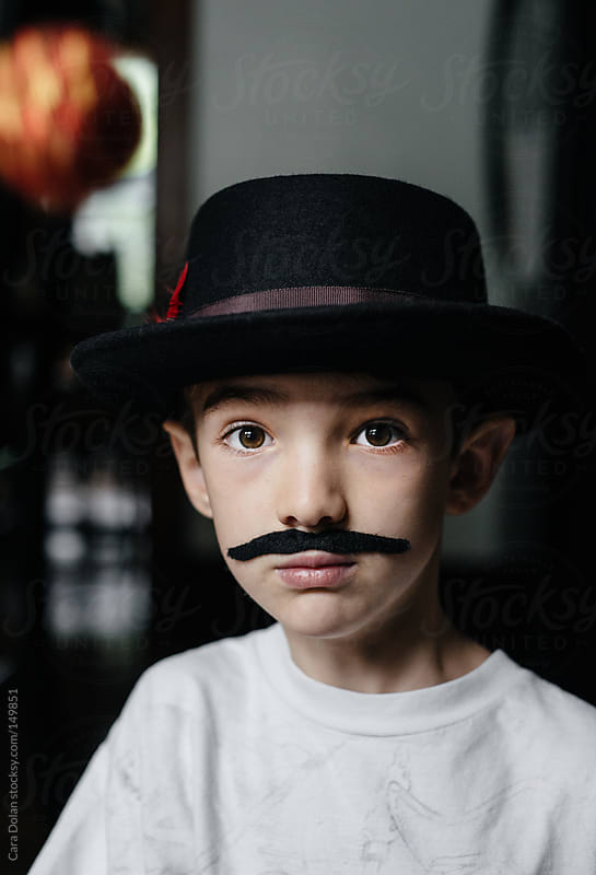 Portrait of a boy wearing a vintage hat and fake mustache by Cara Dolan for Stocksy United