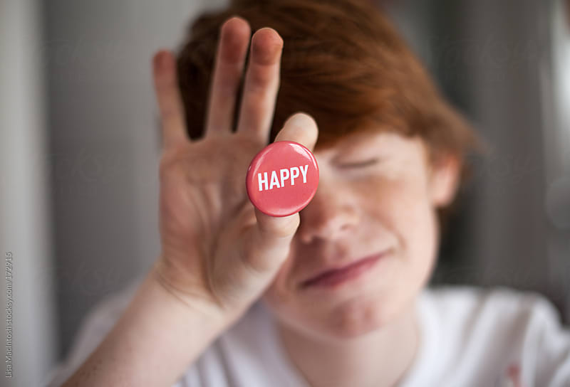 red haired boy holding red pin that says 'happy' by Lisa MacIntosh for Stocksy United