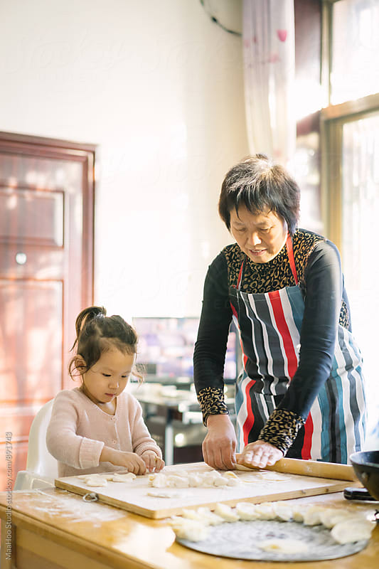 Grandmother and granddaughter making Chinese dumplings by MaaHoo Studio for Stocksy United
