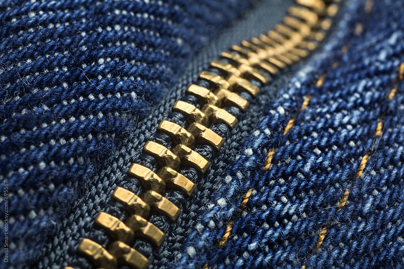 Macro showing teeth of a zipper on a pair of jeans by David Smart for Stocksy United