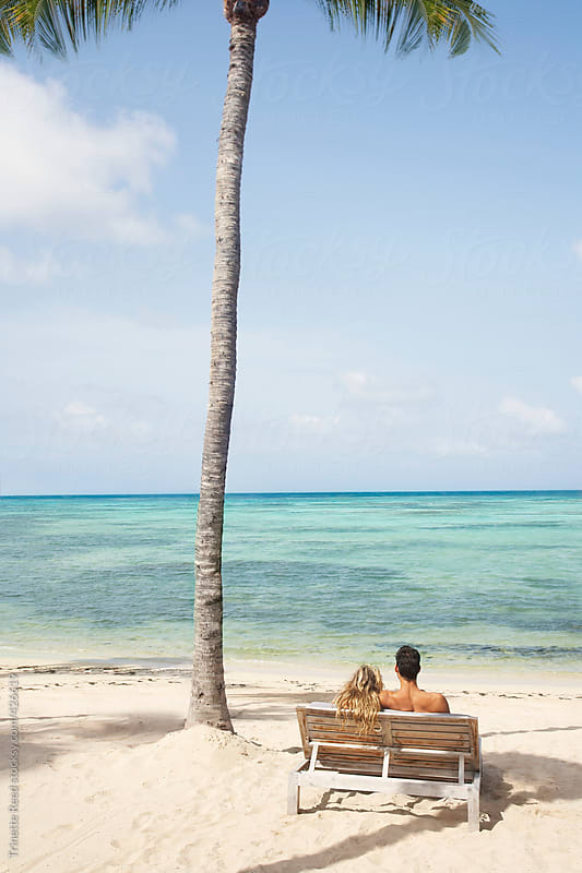 Couple relaxing on beach on the island of St. Barths  by Trinette Reed for Stocksy United