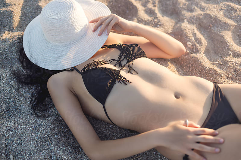 Young Woman Lies on a Sandy Beach Hiding under a Hat by Helen Sotiriadis for Stocksy United