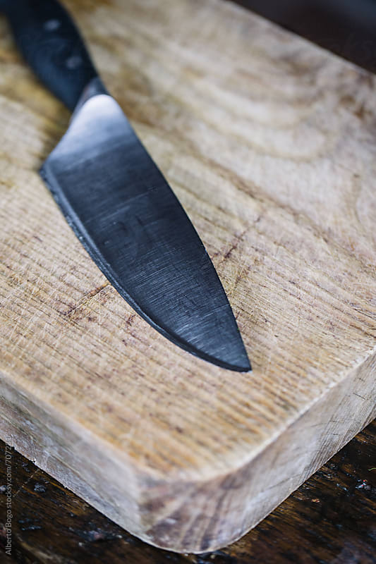 Knife on wooden cutting board by Alberto Bogo for Stocksy United