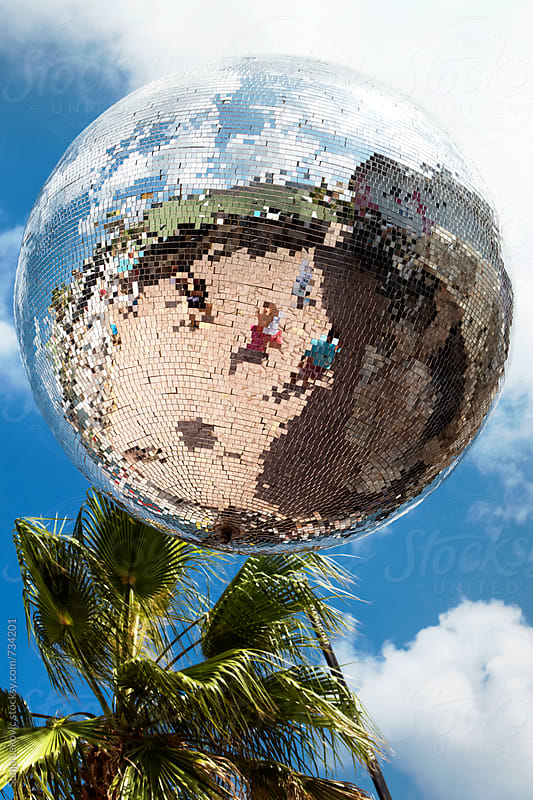 disco ball, palm tree and blue sky by Sonja Lekovic for Stocksy United