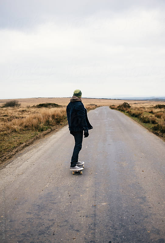 Man riding a skateboard along a country road by Suzi Marshall for Stocksy United