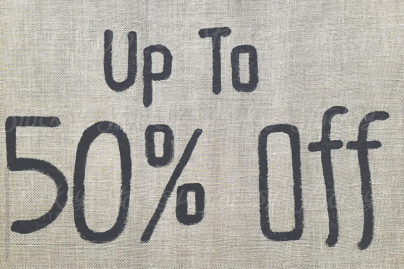 Sign on a retail store offering 50 percent discount. by Shikhar Bhattarai for Stocksy United