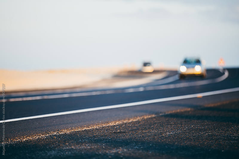 Close up of a road in the desert with two blurry cars in the background by Alejandro Moreno de Carlos for Stocksy United