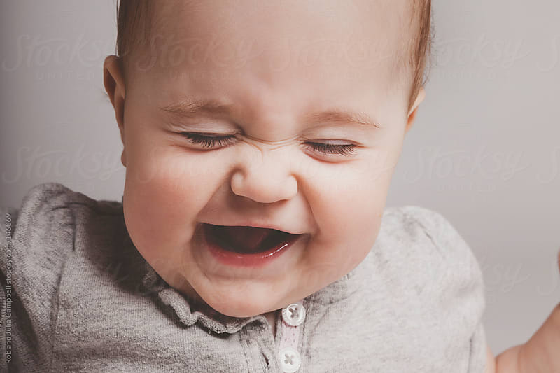 Cute baby girl laughing on solid background by Rob and Julia Campbell for Stocksy United
