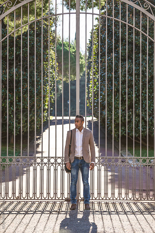 Black businessman standing in front big gate in the park. by BONNINSTUDIO for Stocksy United
