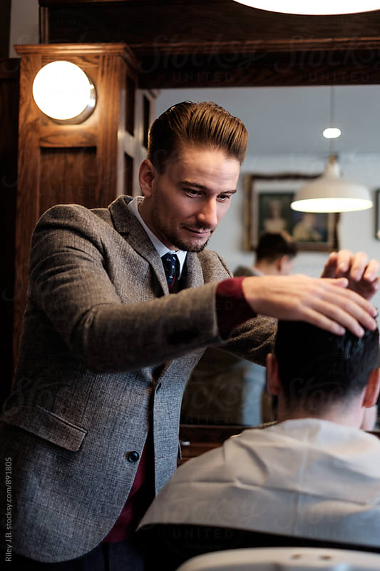 A gentleman barber inspects a client's hair before a cut. by Riley J.B. for Stocksy United