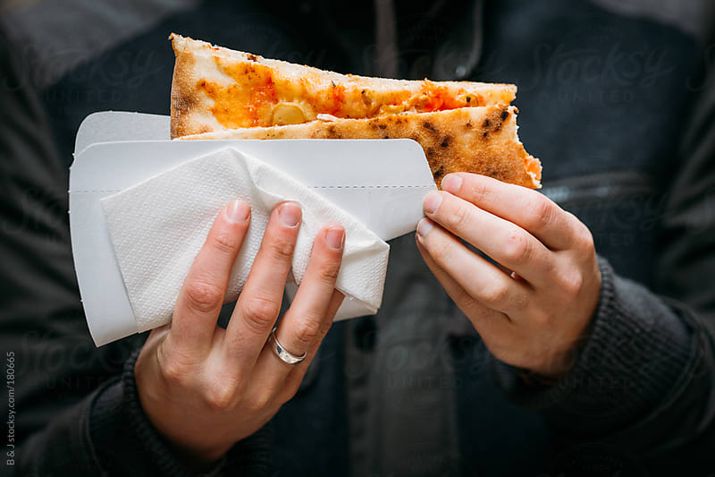 A guy is eating pizza. by B & J for Stocksy United