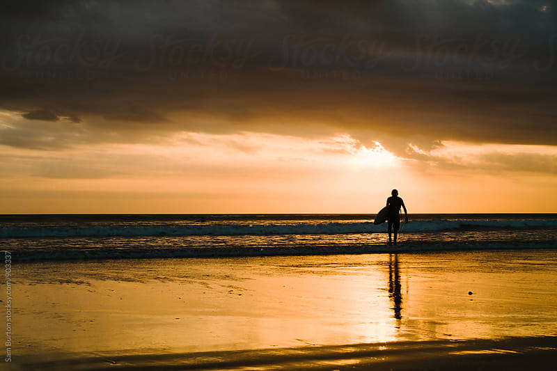 Surfer at sunset by Sam Burton for Stocksy United