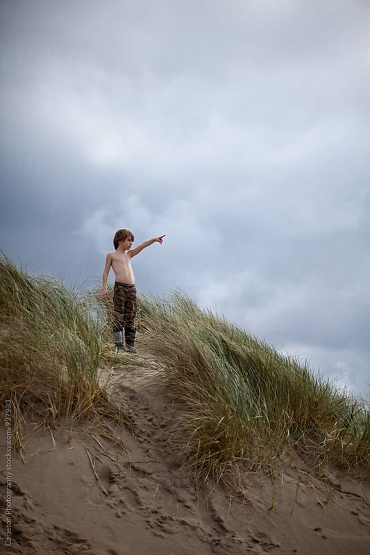 Boy on sand dune points to something unseen  by Carleton Photography for Stocksy United