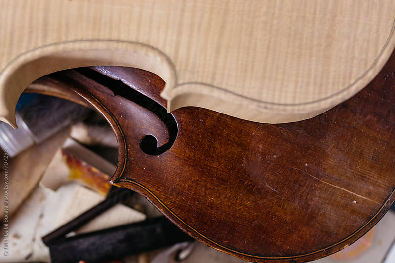Unfinished and finished violin bodies on a workbench by Gabriel (Gabi) Bucataru for Stocksy United