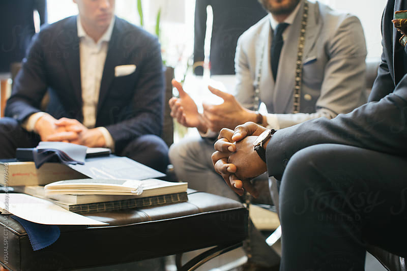 Men's Fashion Store - Two Young Customers Sitting and Conversing With Tailor by VISUALSPECTRUM for Stocksy United