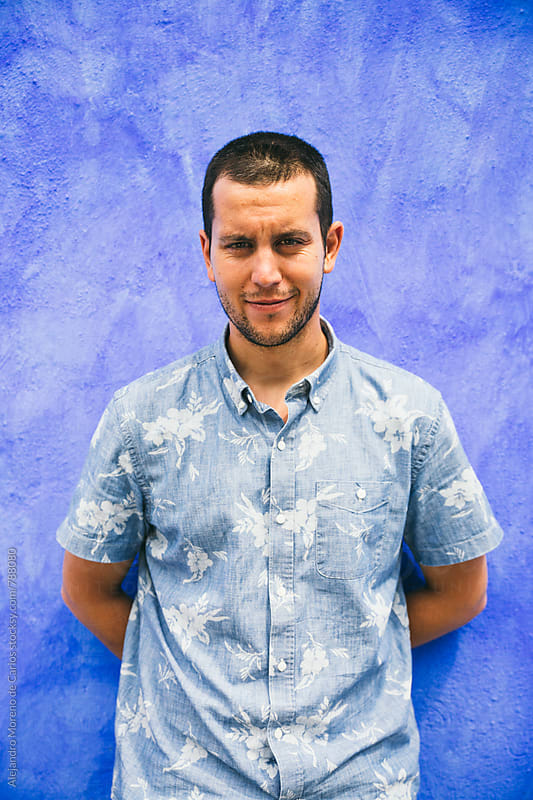 Young man portrait leaning on a blue painted wall as background by Alejandro Moreno de Carlos for Stocksy United