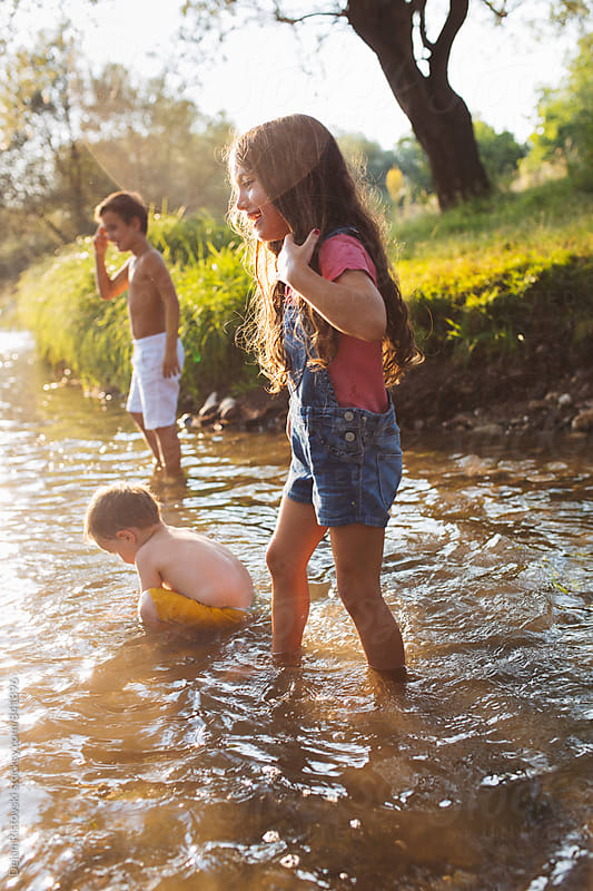 Summer playing at the river. by Dejan Ristovski for Stocksy United